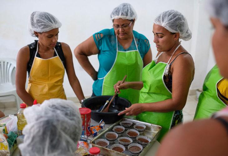 Drei Frauen stehen um einen Küchentisch und Backen