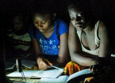Kindern sitzen im Dunkeln mit Schulbüchern und Solarlampe