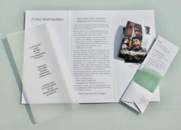 Weihnachts-Anstatt-Billet im aufgeklapptem Zustand mit Transparentpapier und Seifenpäckchen.