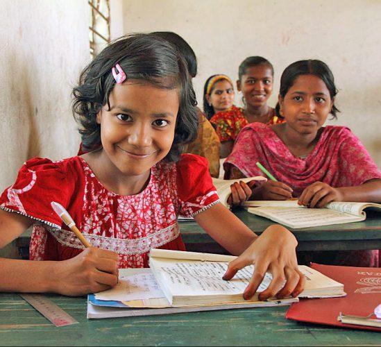 Mädchen in Schulklasse mit Stift und Buch