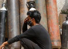 verzweifelter, hockender Mann vor Sauerstoffflaschen