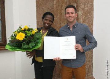 Mann und Frau halten die erhaltene Urkunde und einen Blumenstrauß in der Hand