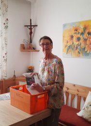 Frau mit Postversandbox und Aussendungsmaterial