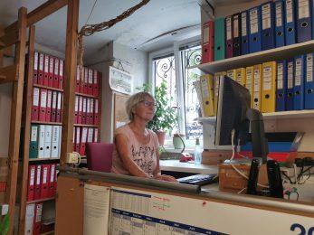 Frau vorm Computer sitzend mit Ordner im Hintergrund