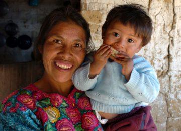 Indigene Frau mit kleinem Kind auf dem Arm, der etwas isst.