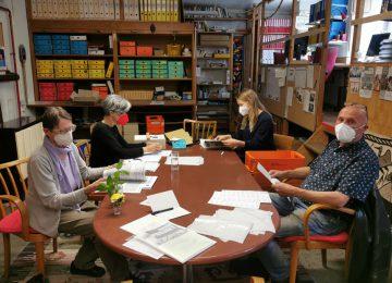 Ehrenamtliche MitarbeiterInnen arbeiten am Tisch um unsere Klubzeitung zu versenden